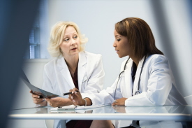Female doctors discussing patient x ray films.